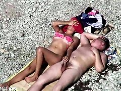 Spy cam video of curvy mature chick giving handjob to her hubby on beach