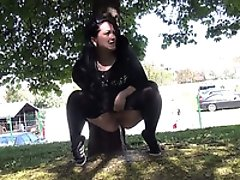 Amateur raven haired chick crouches behind the tree to pee outdoors