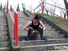 Sporty jogging brunette nympho pisses right on concrete steps