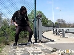 Dressed in all black brunette in sunglasses pisses near the road