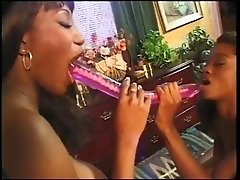 Two black sexy lesbians share one double ended dildo on camera